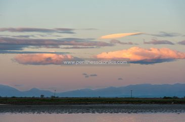 The daybreak colors the clouds and the water of the lagoon.  The lagoon of Kalochori, Thessaloniki / Greece, 25.04.2016. © Aris Papadopoulos